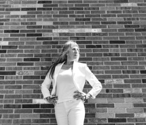 Amy in white against brick wall